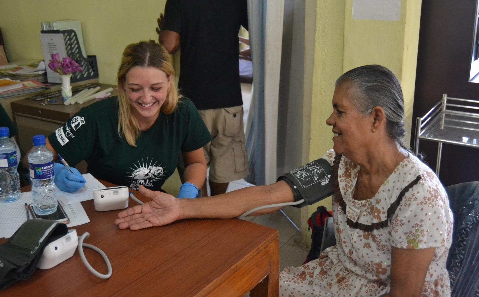 A volunteer on an alternative project to Doctors without Borders takes a patient's blood pressure reading